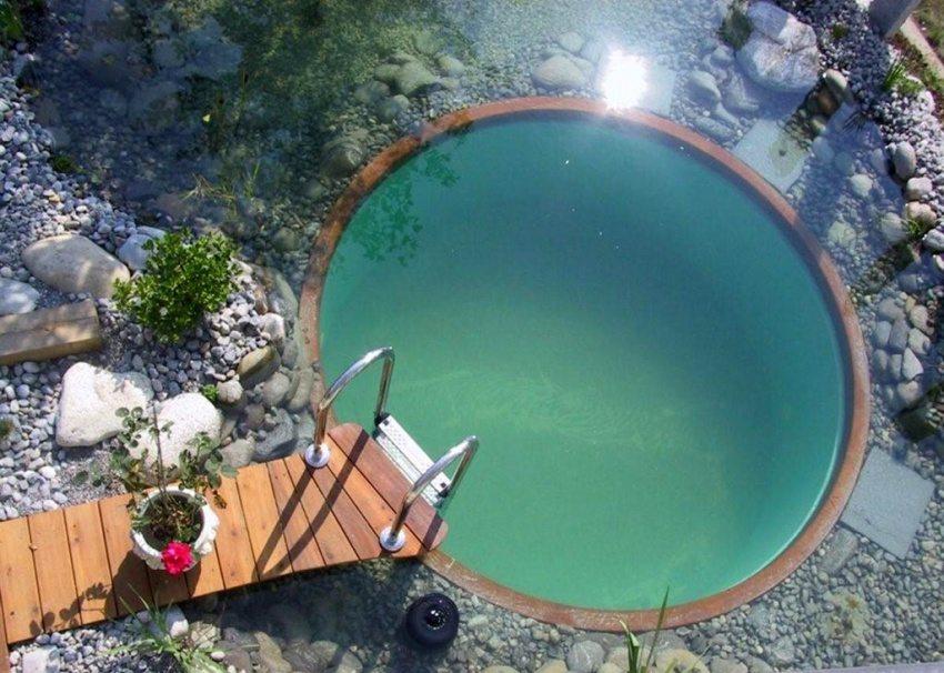 Круглый бассейн с небольшим деревянным мостиком