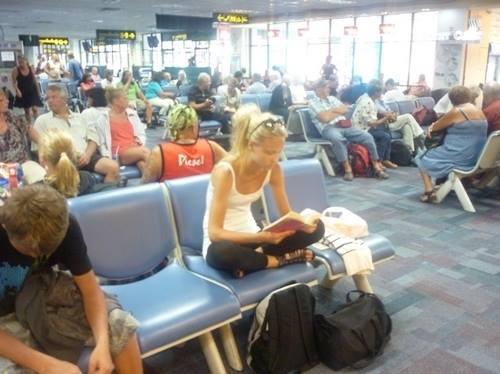 Девушка ожидала свой рейс в большом аэропорту.