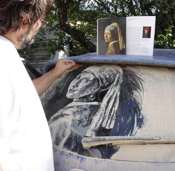 Мужчина рисует на грязном стекле автомобиля