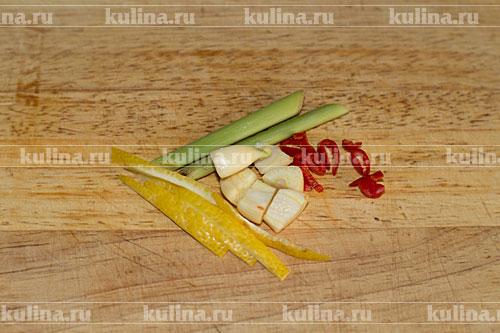 Чеснок разрезать пополам, цедру лимона нарезать полосками, острый перец очистить от семян, шпарить и мелко нарезать.