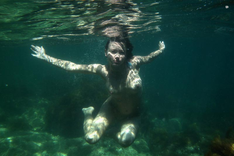 Голые под водой плывут девушки