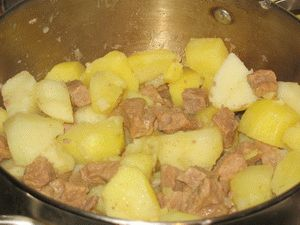 перемешать тушёную картошку с мясом
