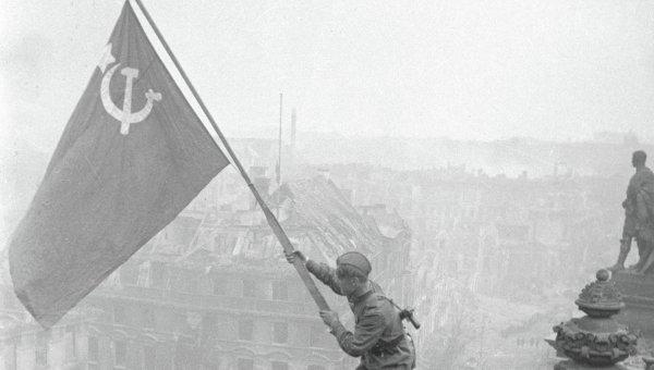 Боец Красной армии водружает Знамя Победы на поверженном рейхстаге. Архивное фото