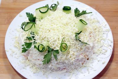 Посыпать сверху салат тертыми отварными желтками яиц и украсить зеленью, ломтиками свежего огурца