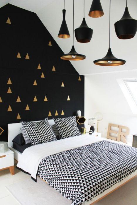 Чёрная стена с золотым декором перекликается с модными светильниками