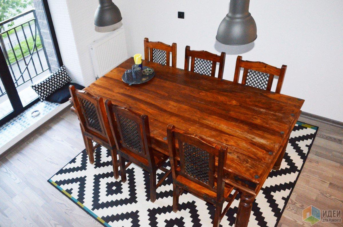 Деревянный обеденный стол, ковер с геометрическим узором
