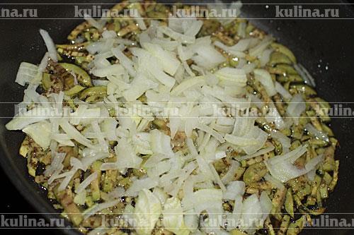 Репчатый лук нарезать и добавить к баклажанам.