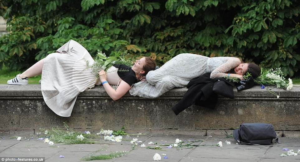 It all got a bit too much for these two party-goers who stopped for a nap on a wall after swapping their heels for trainers