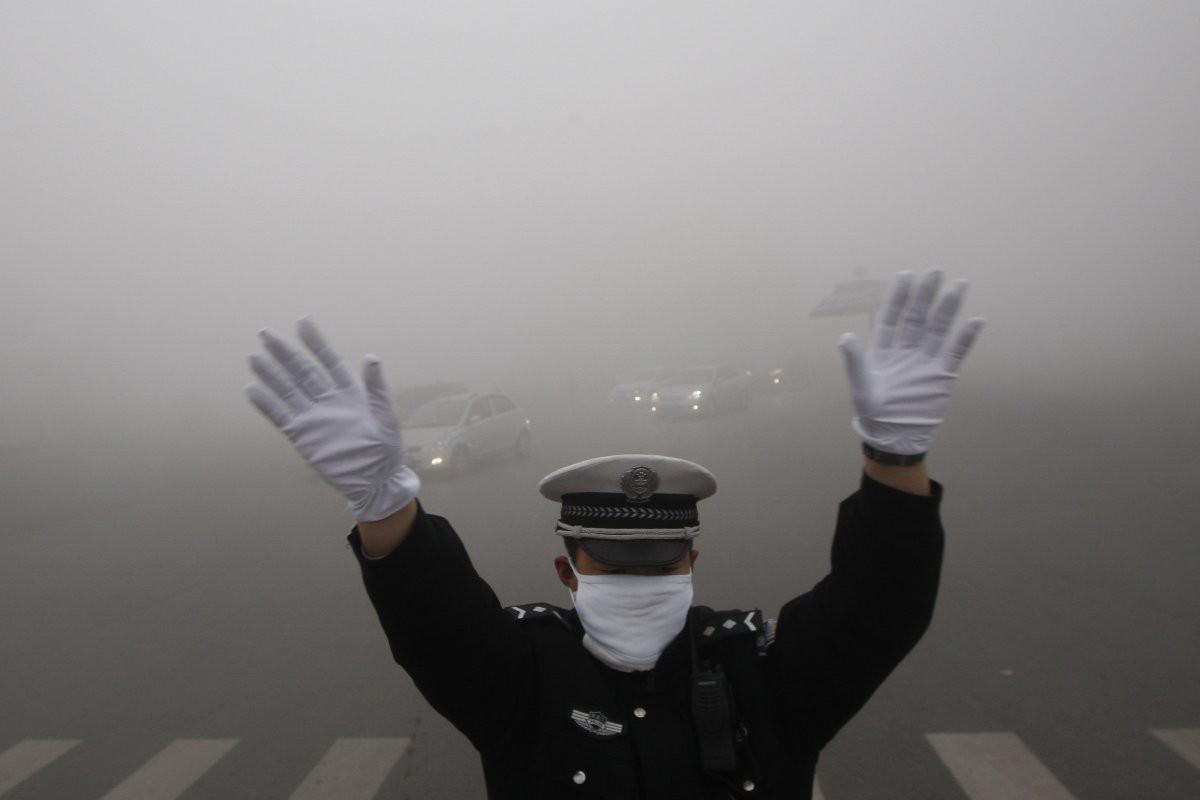 Сотрудник дорожной полиции города Харбин на посту. Только фары позади него можно разглядеть загрезнение, китай, природа