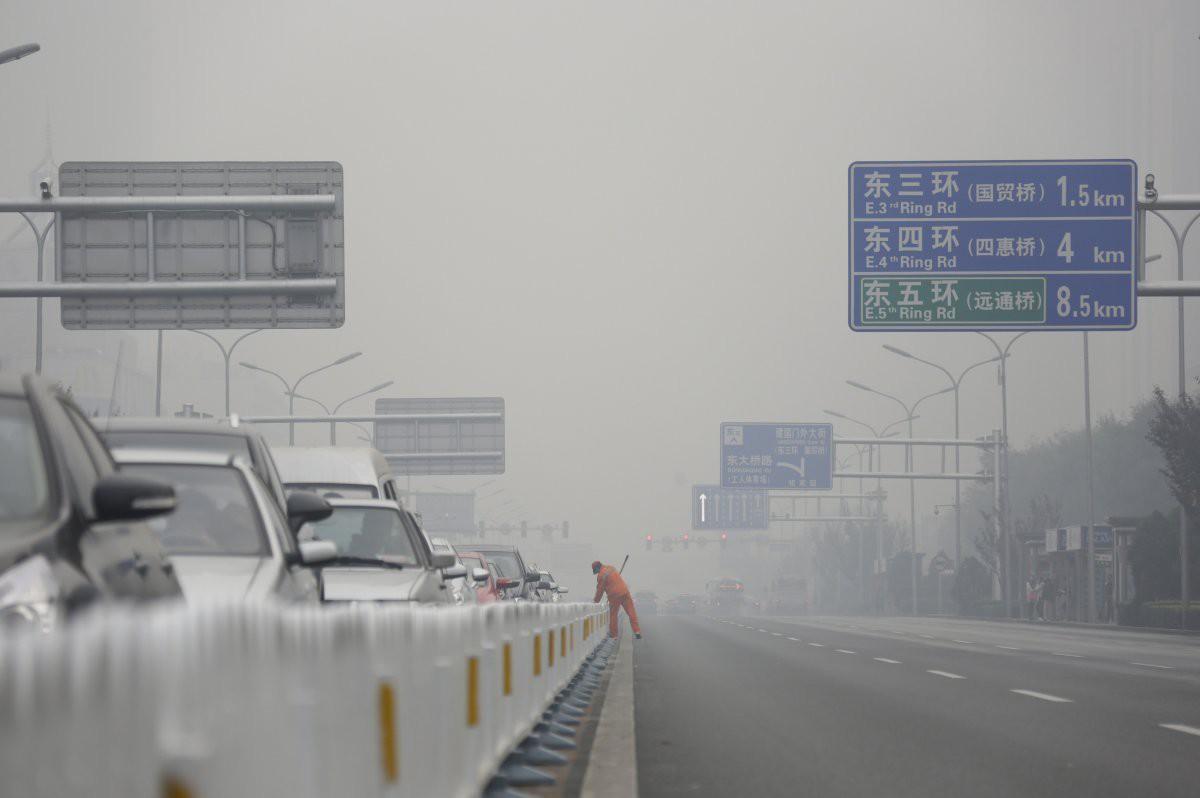 Уборщик на главной дороге в центре Пекина загрезнение, китай, природа