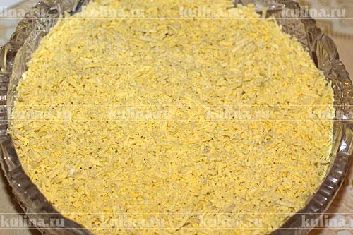 Следующий слой - натертые на мелкую терку желтки яиц.