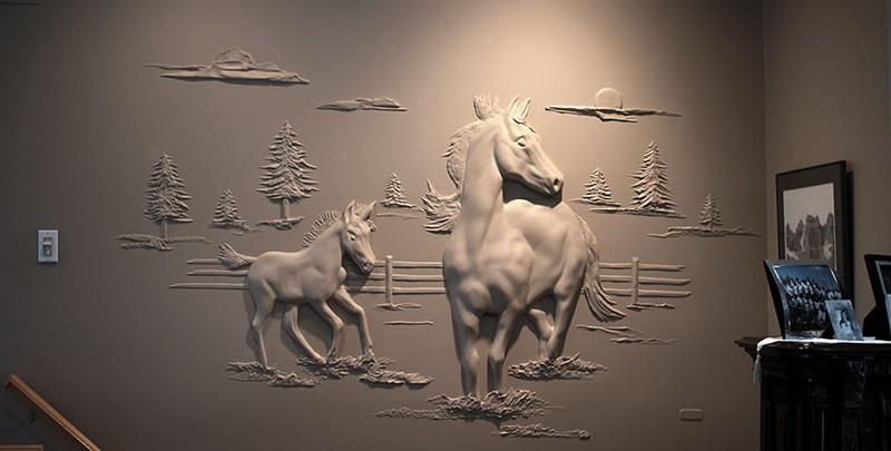 Рабочий украшает гипсокартоновые стены объемными картинами, используя лишь шпатлевку