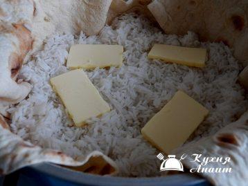Сверху выкладывать частями рис, чередуя кусками сливочного масла.