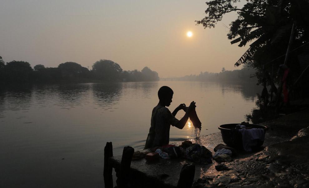 Женщина стирает одежду в реке