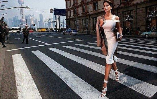 Хорошо одетая молодая женщина идет по улице. Улыбнемся))