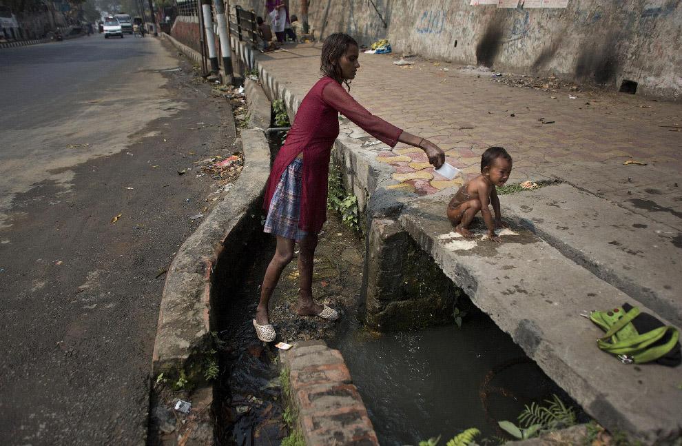 Принятие душа из сточной канавы в Индии