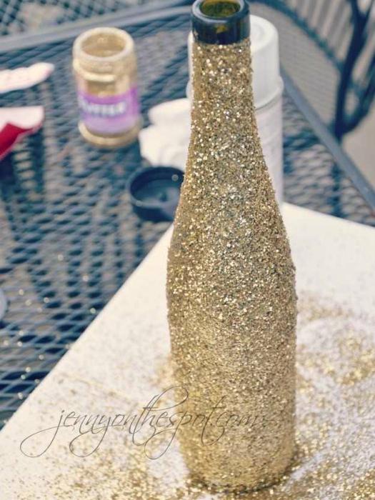 Идеи превращения винных бутылок в стильные и функциональные: Блестящая ваза. Покройте винную бутылку клеем и обсыпьте сверху блестками.