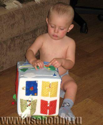 малыш играет с развивающим кубиком ручной работы