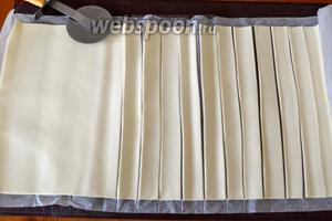 Тем временем слоёное тесто развернуть и нарезать полосками 1,5-2 см.