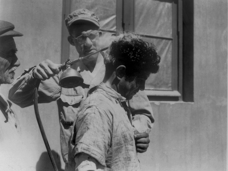 This historic image depicts a U.S. soldier as he was in the process of demonstrating dichlorodiphenyltrichloroethane, or DDT hand-spraying equipment, used to apply this insecticide to an unidentified recipient's head