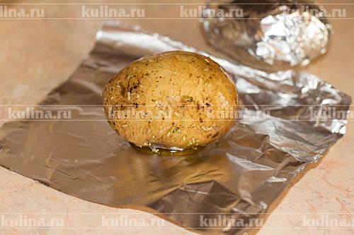 Разрезать фольгу на 5 листов, положить на каждый картофель и завернуть. Положить картофель на противень.