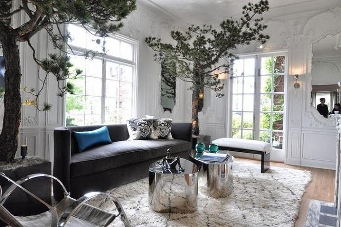 Причудливый интерьер гостиной комнаты с невероятными деревьями по углам и симпатичными круглыми столиками.