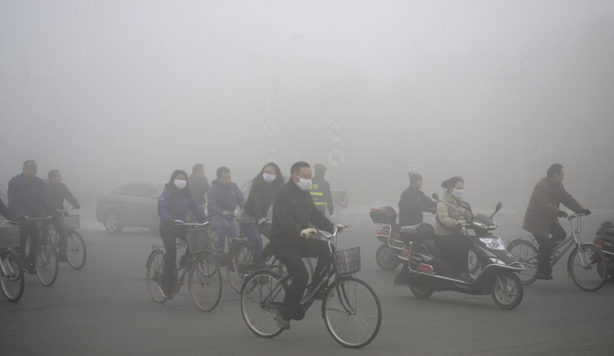 Группа велосипедистов и мотоциклистов носит маски, передвигаясь по улице в городском округе Дацин загрезнение, китай, природа
