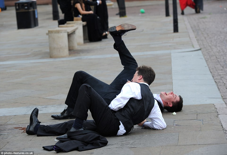 One too many? Two tuxedo-clad male students end up in a pile on the floor after partying until the wee hours