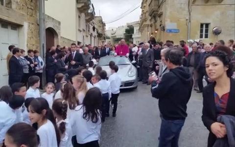 Десятки детей тащили по улице запряженный Порше со священником