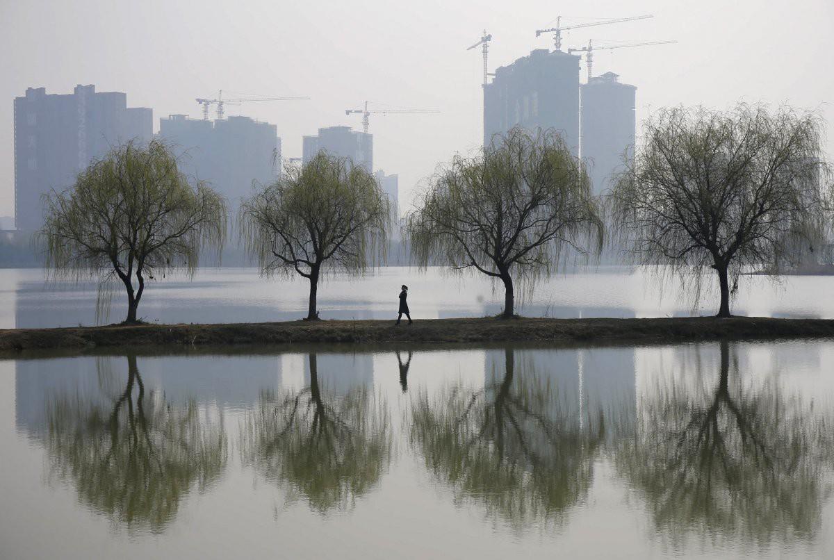 Женщина на фоне строящегося жилого комплекса в городе Ухань загрезнение, китай, природа