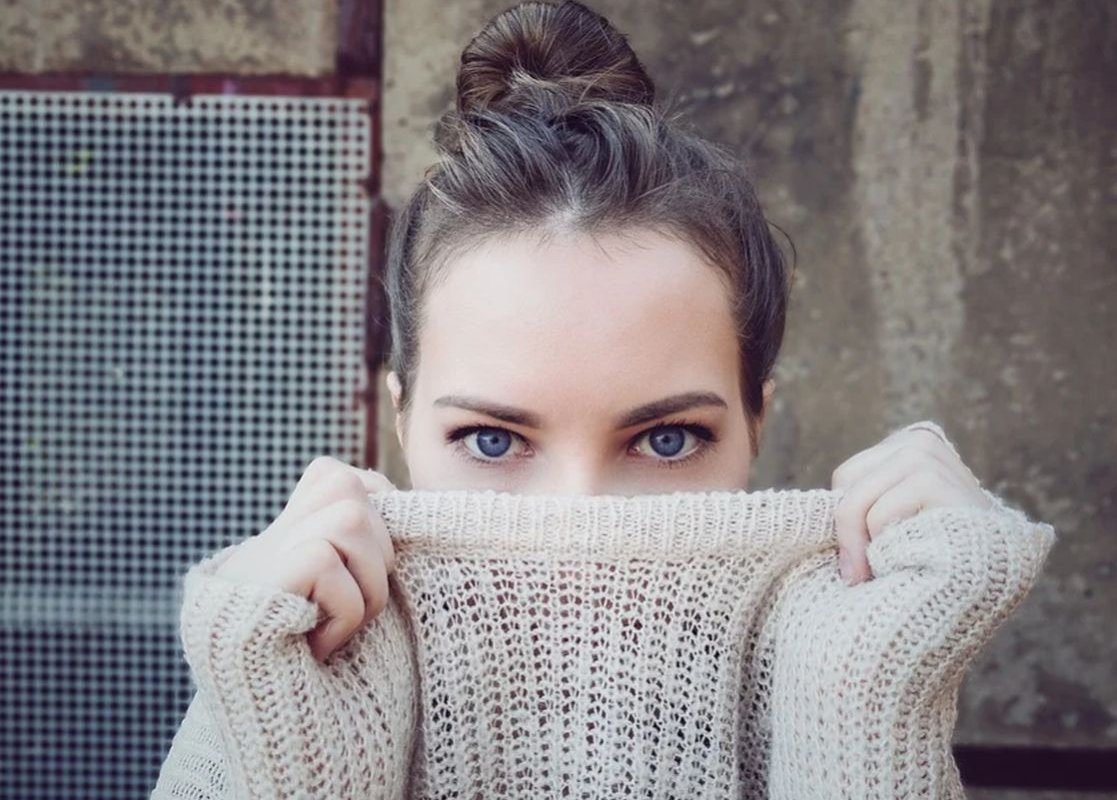 лицо девушки прикрыто свитером