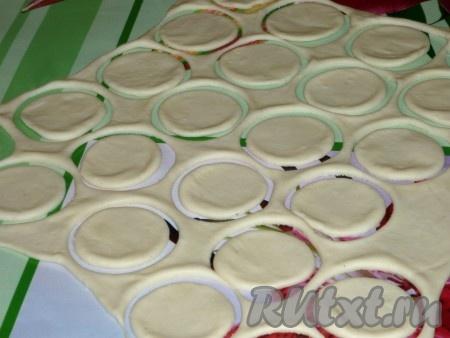 Затем тесто раскатать в тонкий пласт и с помощью рюмки или небольшого стакана вырезать кружочки.