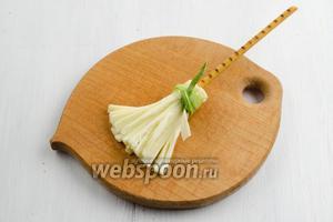 Приложить соломку к целой части куска сыра. Обернуть сыр вокруг соломки. Зафиксировать сырную часть лентой из пера лука.