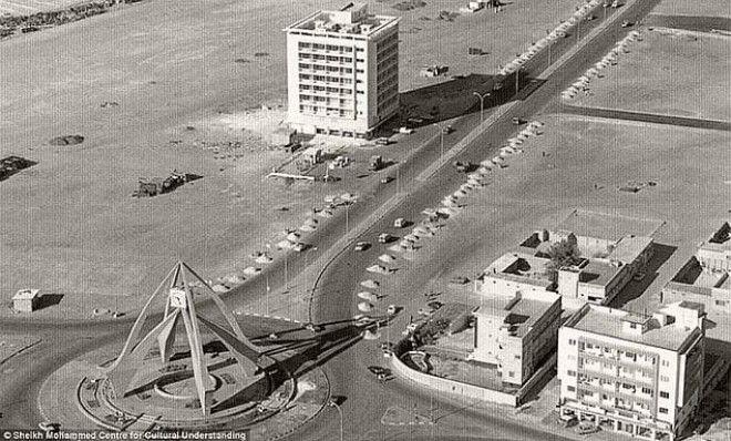 Часовая башня в районе Дейра стоит, окруженная песками и несколькими постройками