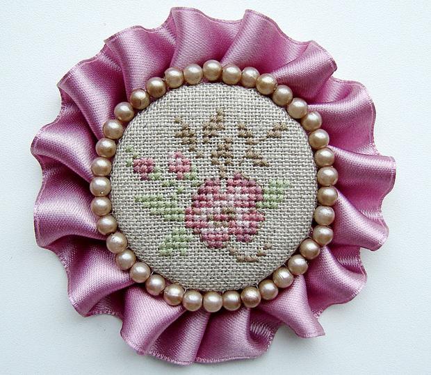 Гламурная ручная брошь в розовых тонах с вышивкой в центре.