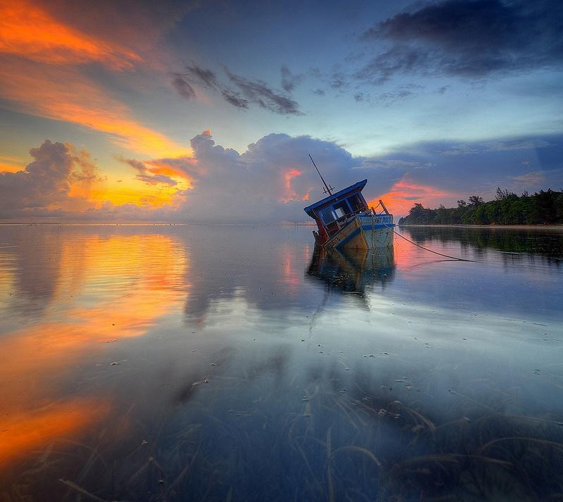 Затонувшая лодка на острове Борнео. Закат. Фото