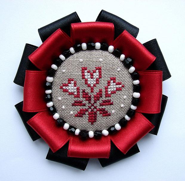 Ручная брошь в черно-красных тонах с вышивкой в центре.