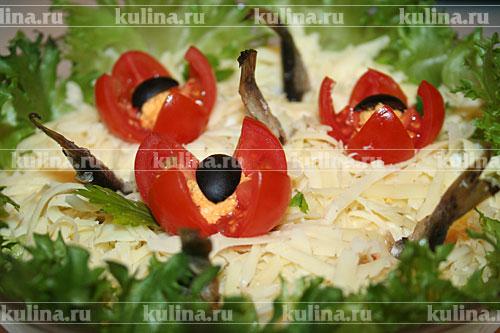 Посыпать салат сыром и украсить по вашему усмотрению оставшимися рыбками, овощами и зеленью.