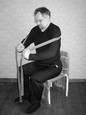 Ременной тренажёр накладывается на область лопаток и плечевых суставов и натягивается так же, как и в предыдущем упражнении и удерживается такое же время. Спина в грудном отделе позвоночника и лопаток выгнута.
