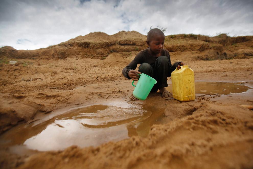 Мальчик собирает воду для питья из луж