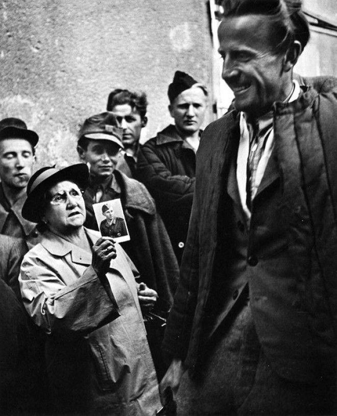 16 Мать показывает фотографию своего сына освобожденному заключенному после окончания Второй Мировой Войны война история память