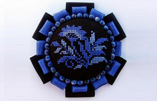 Ручная брошь с вышитым крестиком цветком в центре и оформлена по краю лентами и бисером