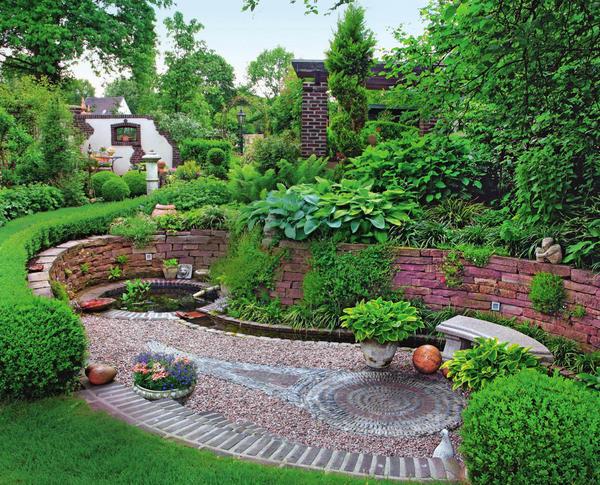 Садовый уголок у основания склона оформлен с большой фантазией