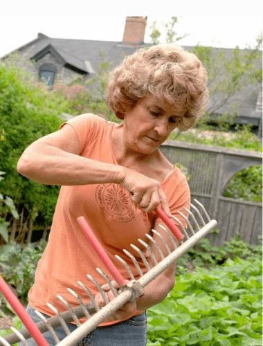 женщина держит в руках грабли