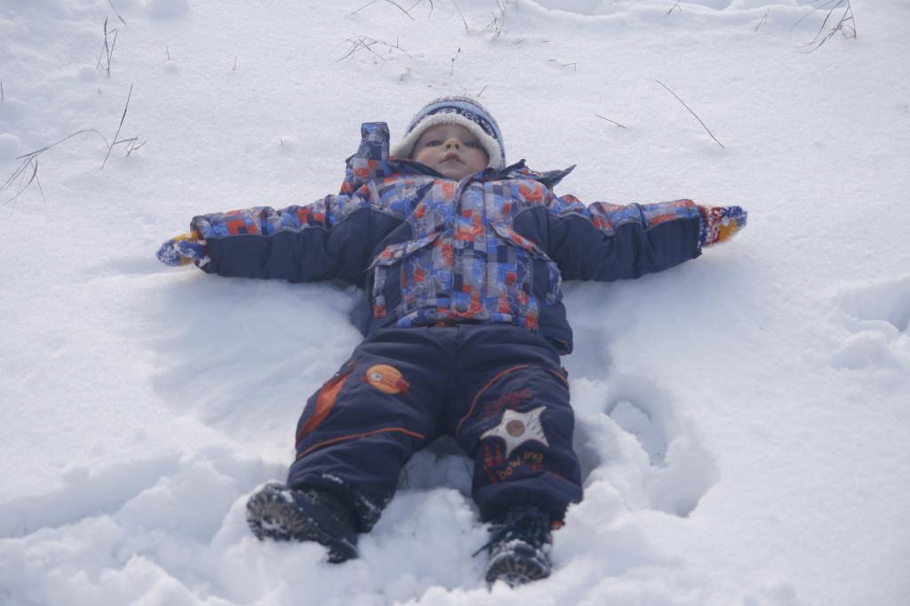 ребёнок лежит на снегу