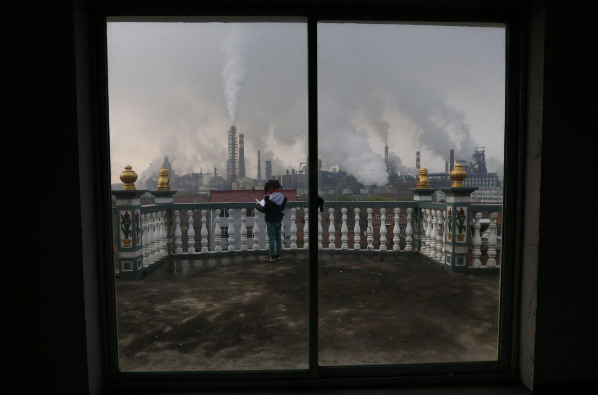 Дым, вздымающийся из металлургического завода, и девочка, которая читает книгу на балконе в Цюйчжоу загрезнение, китай, природа