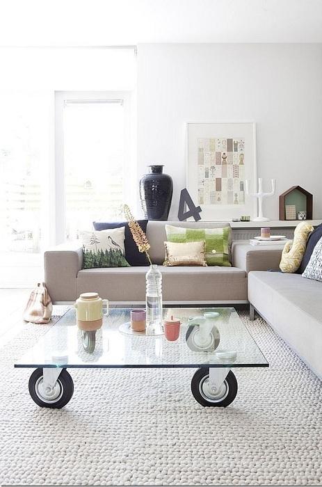 Стеклянный стол отлично вписался в интерьер гостиной комнаты.