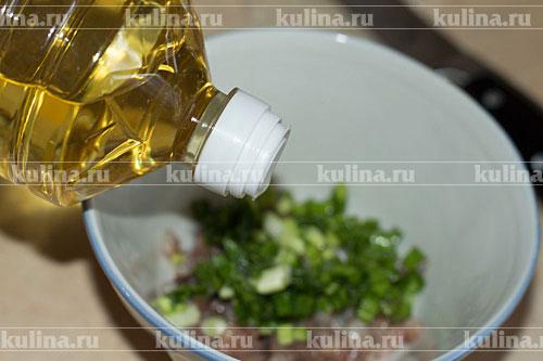 Селедку и зеленый лук мелко нарезать, соединить, заправить растительным маслом.