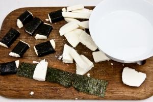 Приготовить миску с водой или соевым соусом. Обмакнуть нори в воде или соусе и завернуть в него сыр. Проделать так со всеми кусочками.