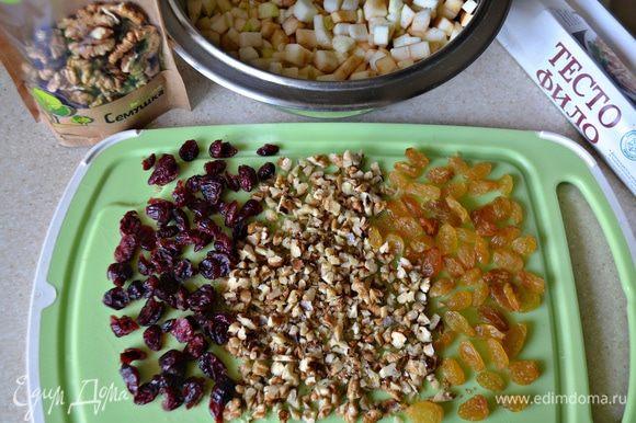 Сухофрукты промойте, просушите, орехи порубите в крупную крошку. Яблоки промойте и нарежьте небольшими кубиками.